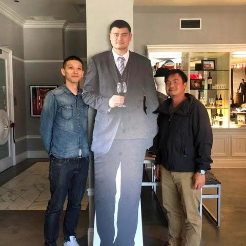Two wine club members posing with Yao Ming cut out.